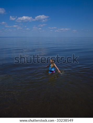 Happy girl wading in the vast blue waters of Lake Superior - stock photo