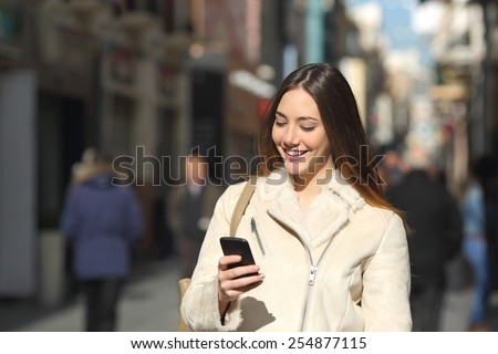 Happy girl walking and texting on the smart phone in the street in winter wearing a white jacket - stock photo