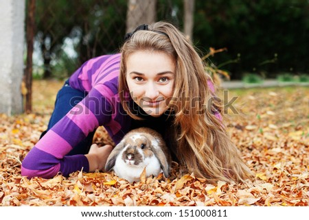 Happy girl walking in autumn park with her rabbit