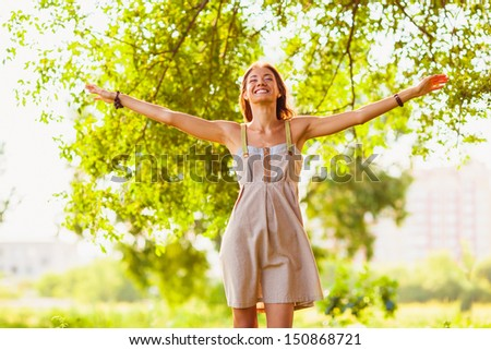 Happy girl walking in green summer park, she raised her hands to the sides - stock photo