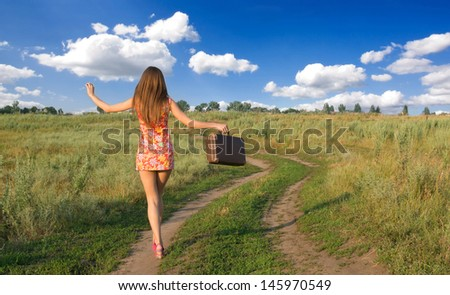 Happy girl walking on the country road with little old fashioned  bag.  - stock photo