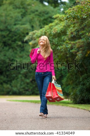 Happy girl walking with bags at the park - stock photo