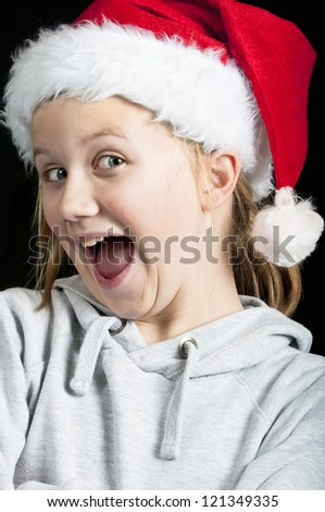 Happy girl wearing a santa hat - stock photo