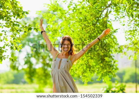 happy girl wearing headphones outdoors and rising her hands - stock photo