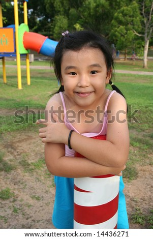 Happy girl wearing pink singlet at the playground - stock photo