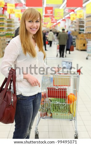 Happy girl wearing white shirt and cart with food; shallow depth of field - stock photo