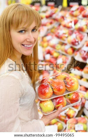 Happy girl wearing white shirt keeps packed apples in store; shallow depth of field - stock photo