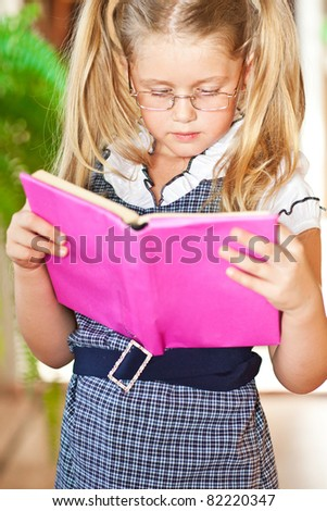 Happy girl with a book with glasses in school is a lesson - stock photo