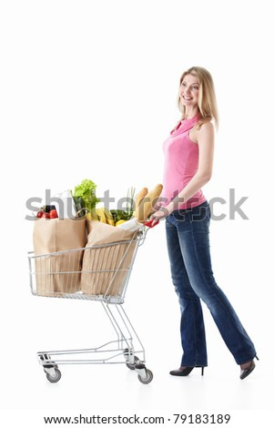 Happy girl with a cart with food on a white background - stock photo