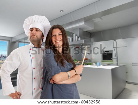 Happy girl with a chef in a modern kitchen - stock photo