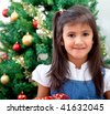 Happy girl with a christmas tree behind indoors - stock photo