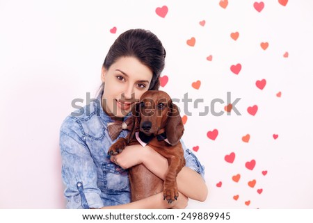 happy girl with a dog dachshund against the background of the heart. close-up, International Women's Day, Valentine's Day  - stock photo