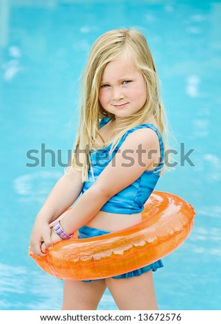 Happy girl with a float ring ready to go swimming - stock photo