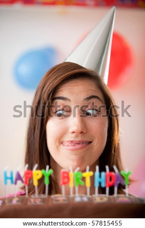 Happy girl with a funny face and a happy birthday cake - stock photo