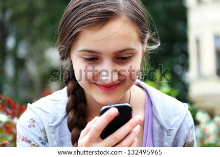 Happy girl with a mobile phone reads the message - stock photo
