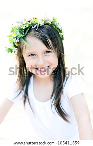 Happy girl with a wreath of flowers. - stock photo