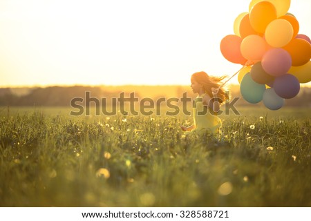 Happy girl with balloons in the field - stock photo