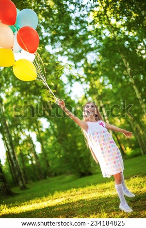 Happy girl with balloons in the summer park. - stock photo
