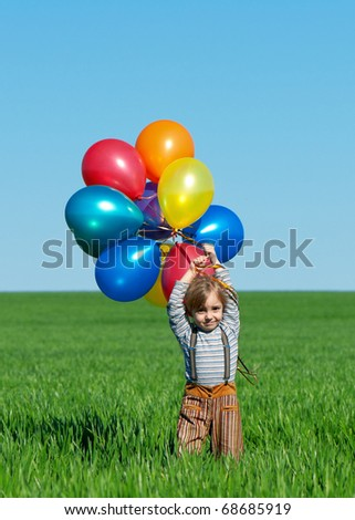 Happy girl with balloons walking on the spring field - stock photo