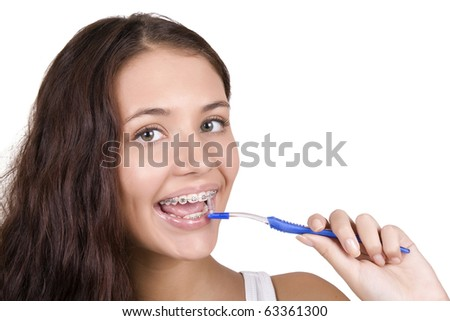 happy girl with braces brushing her teeth
