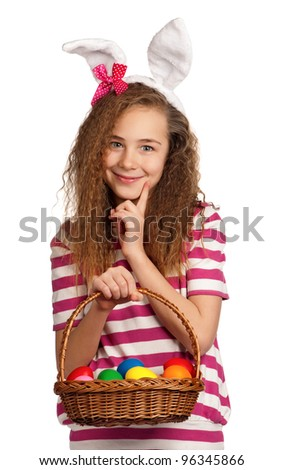 Happy girl with bunny ears, holding basket of eggs isolated on white background - stock photo