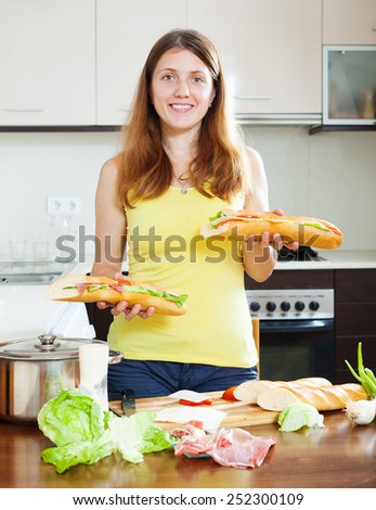 Happy girl with cooked sandwiches in home kitchen