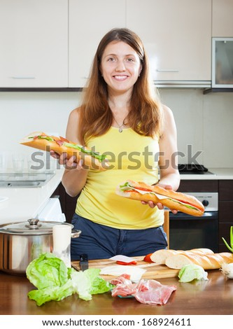Happy girl with cooked sandwiches in  kitchen
