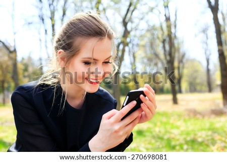 Happy girl with disheveled hair looking into smartphone smiling - stock photo