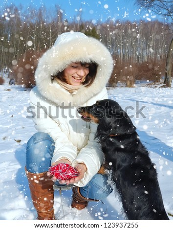 Happy girl with dog in winter park - stock photo