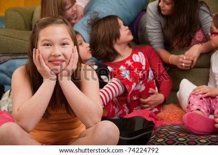 Happy girl with friends seated on floor at a sleepover - stock photo