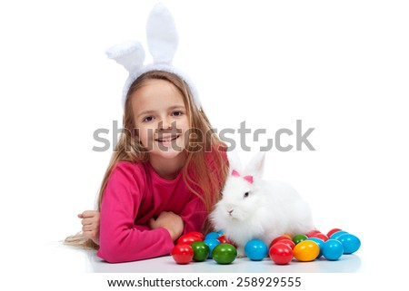 Happy girl with her easter rabbit and colorful dyed eggs - isolated - stock photo
