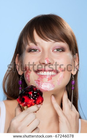 Happy girl with her face smear in cake smiling and looking at camera