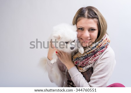 Happy girl with her little dog in studio
