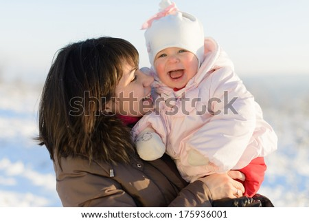 happy girl with her mother walking in winter day - stock photo