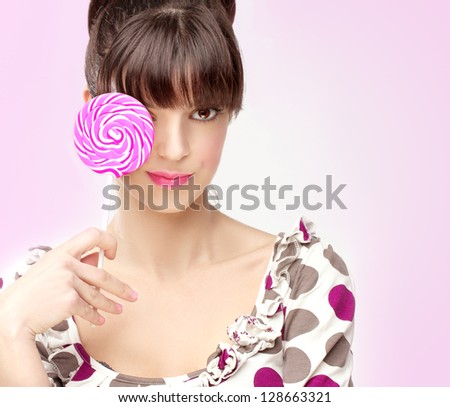 Happy girl with lollipop.Rose background - stock photo