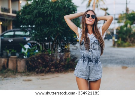 Happy girl with long dark hair in glasses hold head and smiles, she is wearing in  denim overalls and white t-shirt  - stock photo