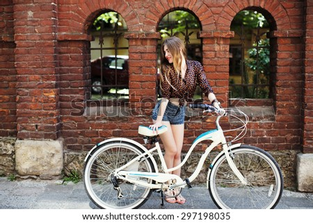 Happy girl with long fair hair wearing on dark blouse and  blue shorts standing with bicycle near the brick building, on the old city street - stock photo