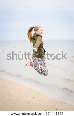 Happy girl with long ponytail jumping on the beach in early morning. Selective focus  - stock photo