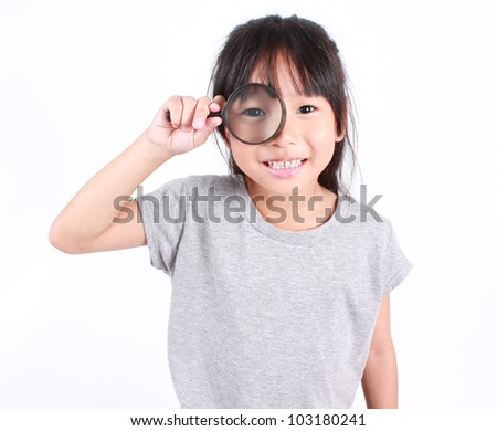 happy girl with magnifying glass - stock photo