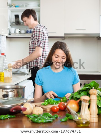 Happy girl with man cooking at table in kitchen