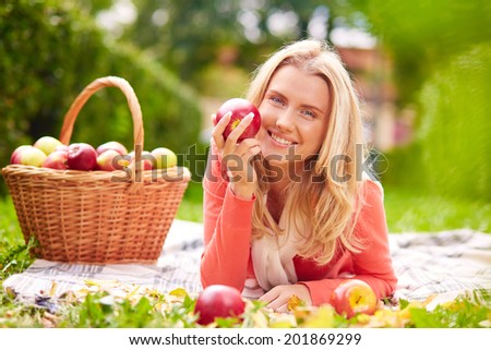 Happy girl with ripe apple looking at camera while lying on grass - stock photo