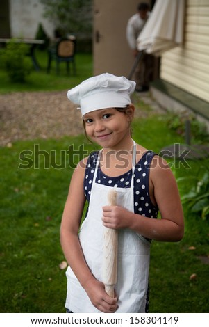 Happy girl with rolling pin (cooking workshop) - stock photo