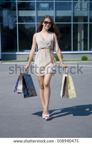 Happy girl with shopping on the street