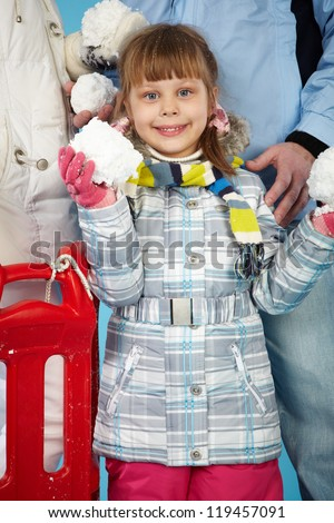 Happy girl with snowballs in hands looking at camera - stock photo