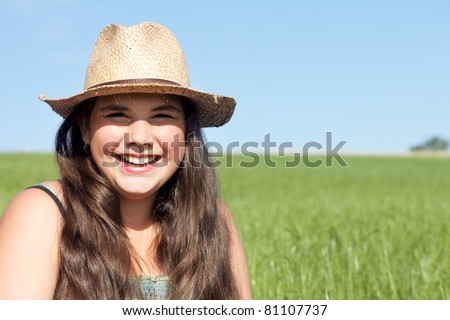 Happy girl with sun hat. Outdoor shot against a blue sky on a fresh green lawn. - stock photo