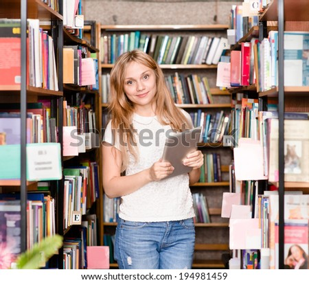 Happy girl with tablet computer in library - stock photo