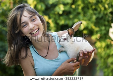 Happy girl with the rabbit outdoors.Photo from a beautiful young woman with her bunny - stock photo