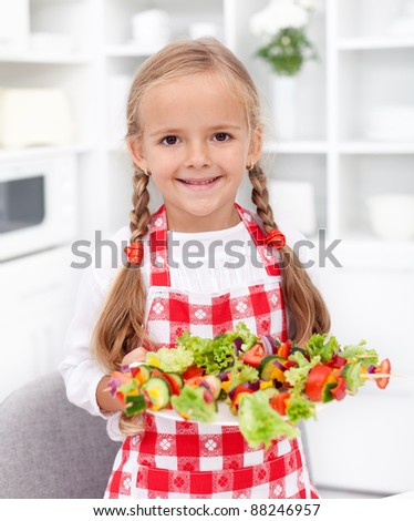 Happy girl with vegetables plate and apron - healthy eating - stock photo