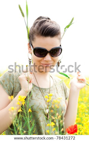 Happy girl with wheat ear around her ears, playing in a blossomed rapeseed field