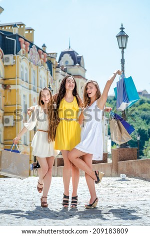 Happy girlfriend enjoyed discounts. Three friends holding shopping bags and raise their hands and buying up outside the shop. Smiling girlfriends having fun together walking on the street - stock photo